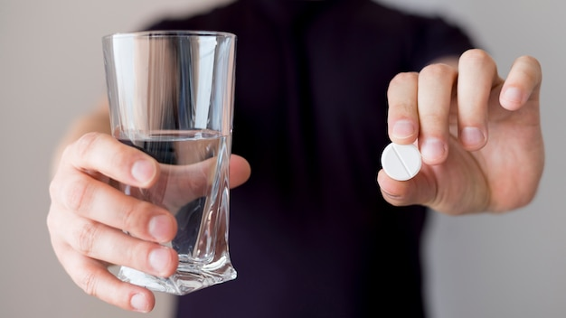 Person holding glass of water and a pill