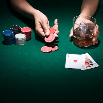 A person holding glass of whiskey while playing poker card