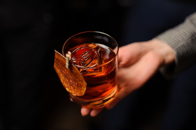 Person holding a glass of whiskey with ice
