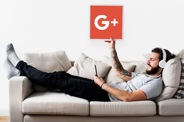 Person holding a google plus icon Free Photo