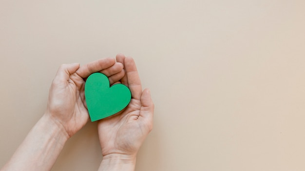 Person holding a green heart on beige background with copy space