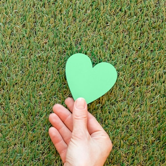Person holding a green heart on grass