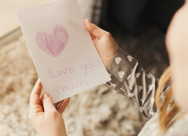 Person holding greeting card with i love you mum inscription