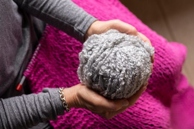 Person holding a grey thread for knitting