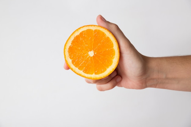 Persona in possesso di metà di frutta arancione