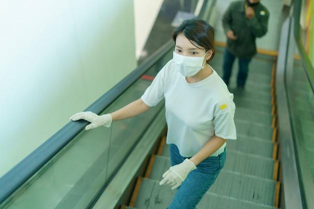 Person holding handrail of escalator