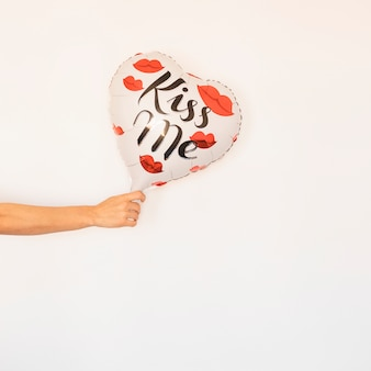 Person holding heart balloon in hand