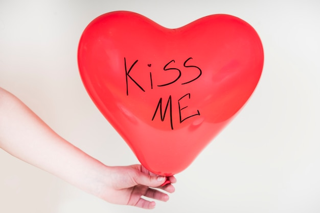 Person holding heart balloon with kiss me inscription