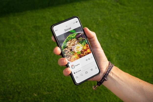화면에 앱이 있는 스마트폰을 들고 있는 사람
