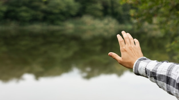 Person holding his hand above lake