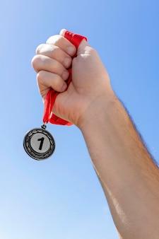 Человек, держащий свою медаль номер один