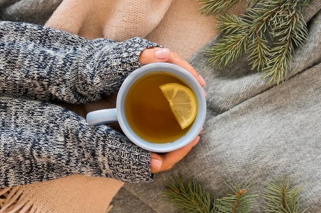 Лицо, держащее горячий чай с лимоном