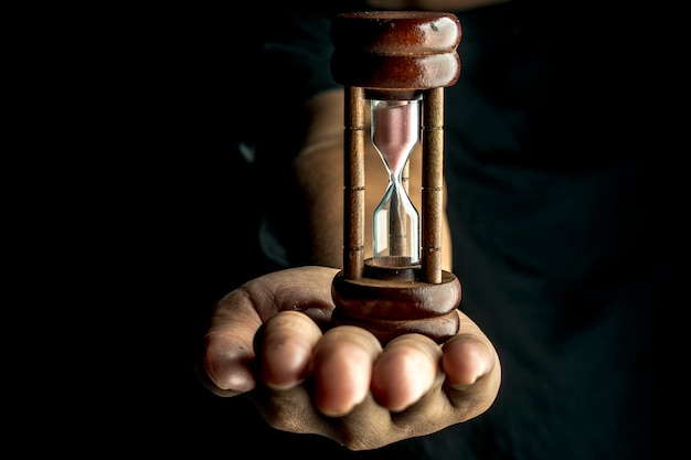 Person holding hourglass against black background
