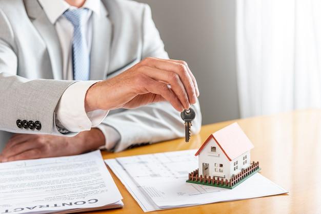 Человек держит ключи от дома и игрушечный модельный дом на столе
