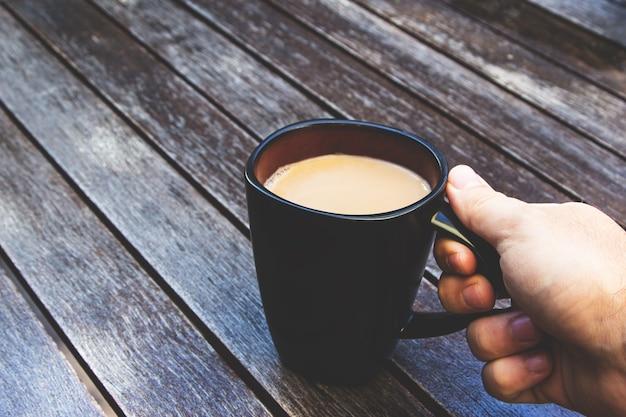 Persona che tiene la sua tazza nera piena di caffè su una superficie di legno