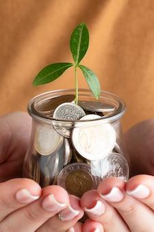 Лицо, занимающее банку монет в руках