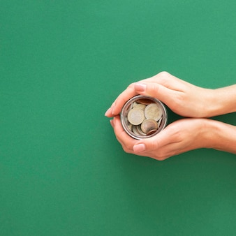 Person holding a jar with coins with copy space