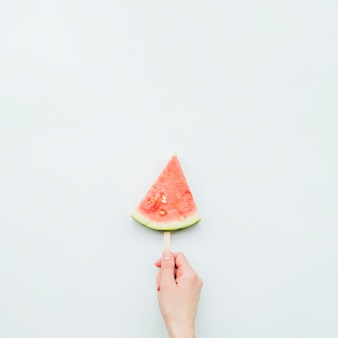 Person holding juicy fresh watermelon popsicle