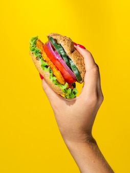 Person holding a juicy veggie burger