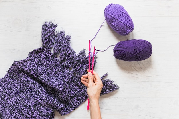 A person holding knitted needles to knit the woolen scarf