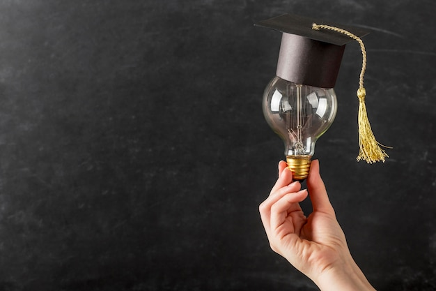 Person holding a light bulb with graduation cap