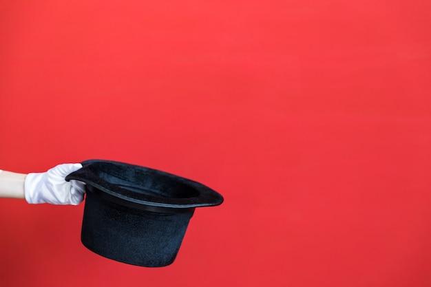 빨간 벽에 마법의 모자를 손에 들고 사람