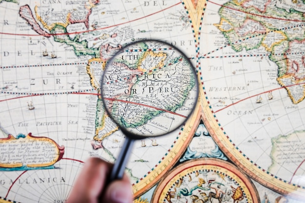 Person holding magnifying glass over map showing peruvian cities