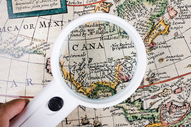 A person holding magnifying glass over map