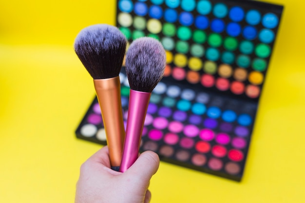 A person holding makeup brush in front of eyeshadow palette on yellow background