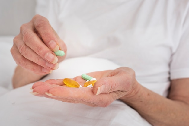 Person holding many colorful pills