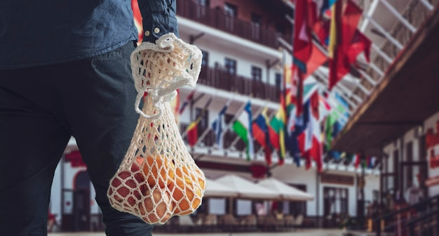 A person holding a mesh eco bag with fresh fruit food from grocery store