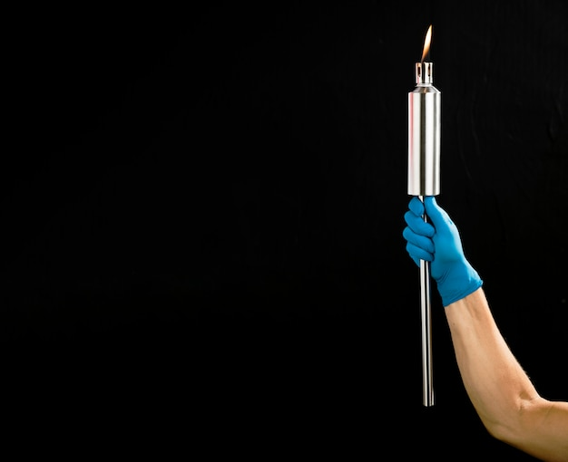 Person holding a metal torch with copy space