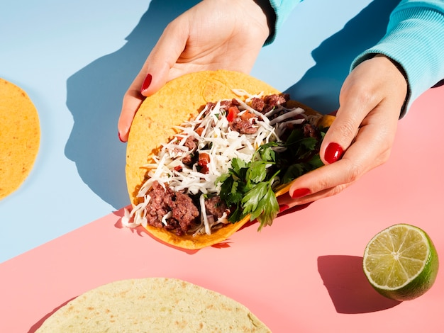 Person holding a mexican taco in hands high view