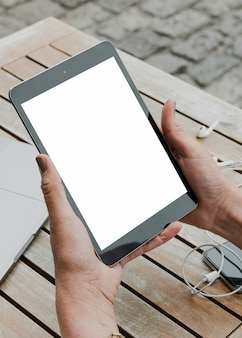 Person holding mockup tablet outdoors