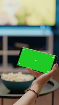 가로 녹색 화면이 있는 현대적인 전화를 들고 있는 사람