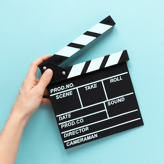 Person holding movie clapper on blue background