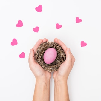 Person holding nest with bright easter egg
