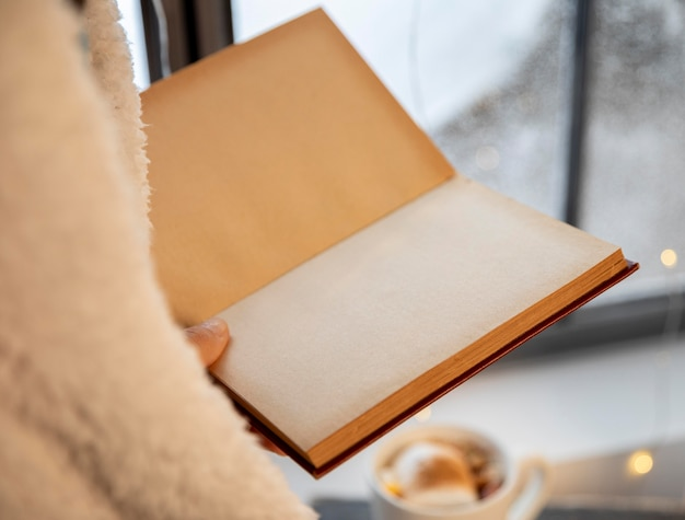 Person holding an opened empty book close-up