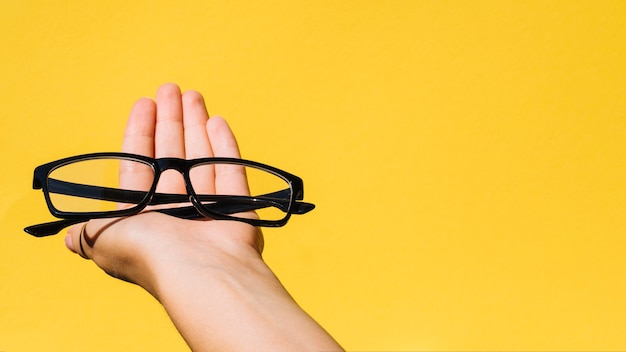 Person holding a pair of eyeglasses with copyspace