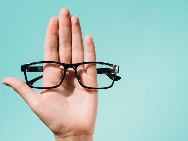 Person holding a pair of eyeglasses