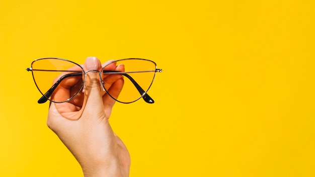 Person holding a pair of modern eyeglasses