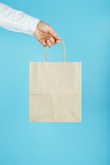 Человек, держащий бумажный пакет