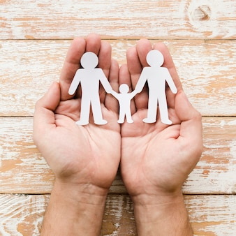 Person holding paper family in hands on wooden background