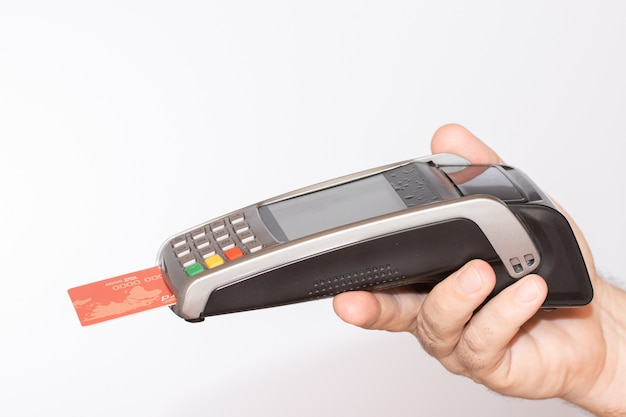 Person holding a payment terminal with a red credit card swiped through the machine