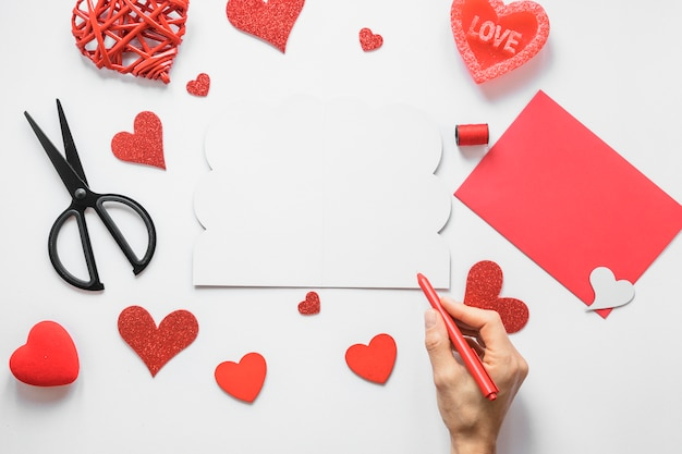 Person holding pen above table with hearts