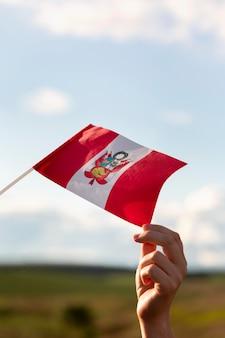 Persona che tiene la bandiera del perù all'aperto