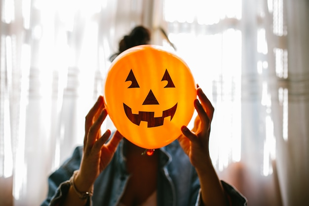 Person holding a pumpkin balloon with her hand and covering her face. young woman celebrating halloween. helium party balloons.