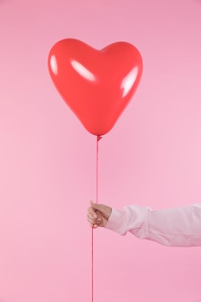 Person holding red balloon with thread