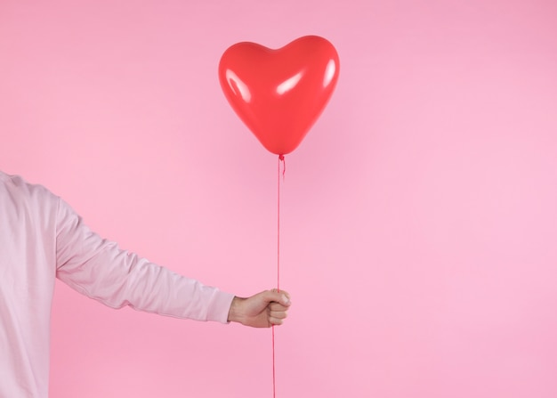 Person holding red balloonwith twist