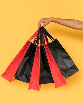 Persona che tiene i sacchetti della spesa rossi e neri